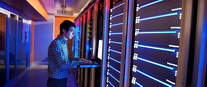 Image showing a man using a computer in the middle of a datacenter room