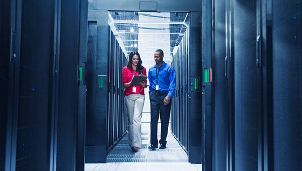 Woman holding a notebook and a man walking inside a server room