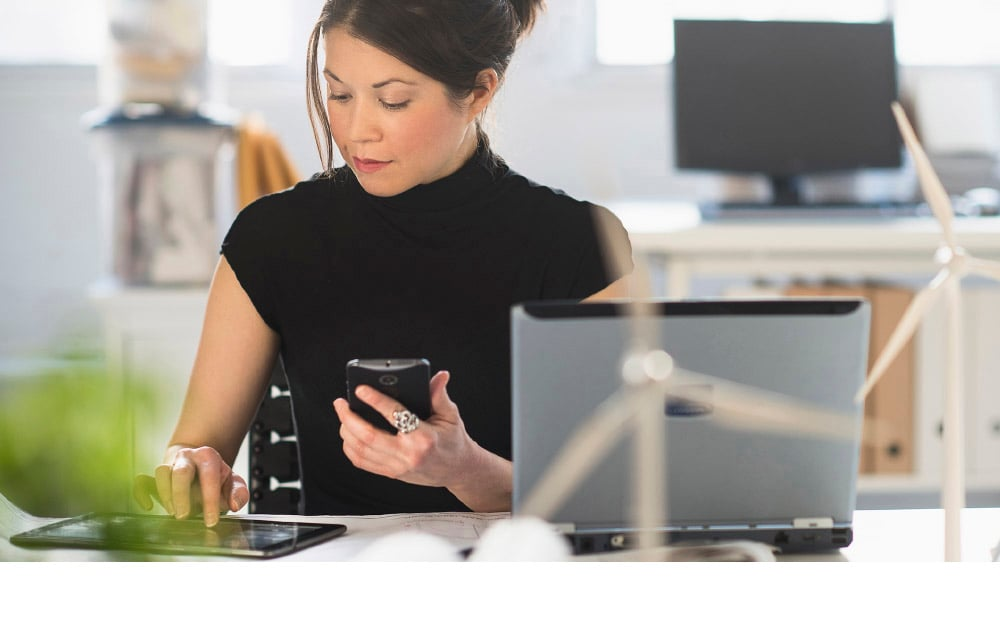Woman working with smartphone, tablet and laptop