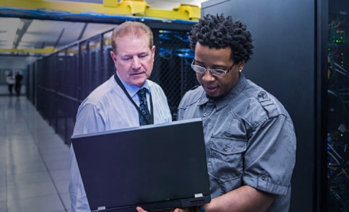 Two people standing on a datacenter room and one of them is holding a laptop