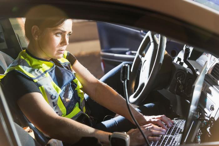 Image depicting a police officer on patrol using the predictive policing platform