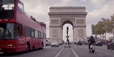 View of the Arc de Triomphe taken from a busy street in Paris