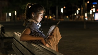 Image of young woman outdoors viewing tablet