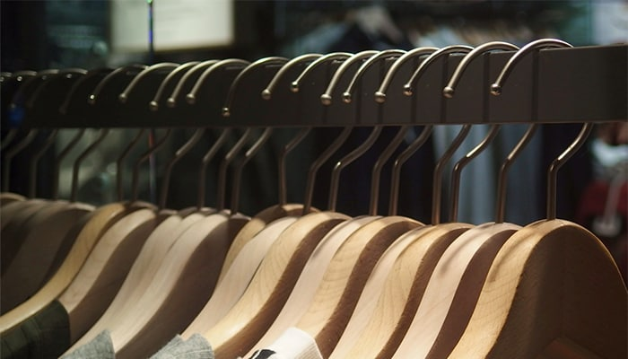 Wooden hangers suspended from a metal clothes rack