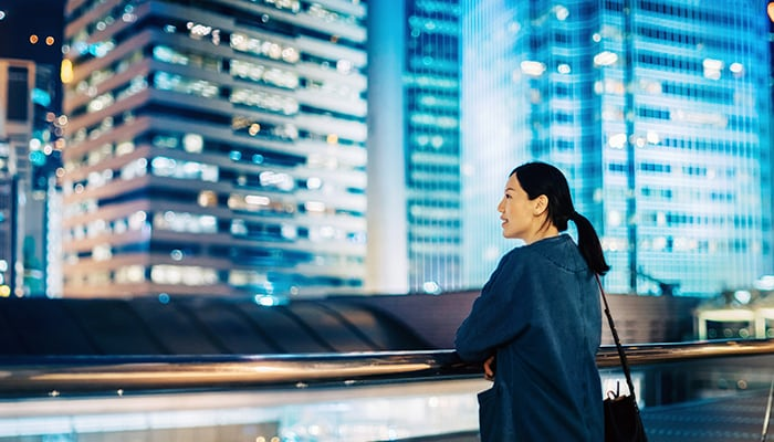 a woman standing on a rooftop overlooking the city at night