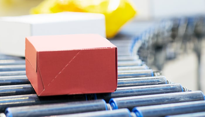 A red box moves across the metal rollers of a conveyor belt