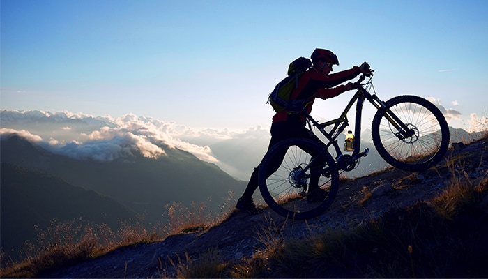 A man wearing a bike helmet and backpack pushes his bicycle up a mountain trail