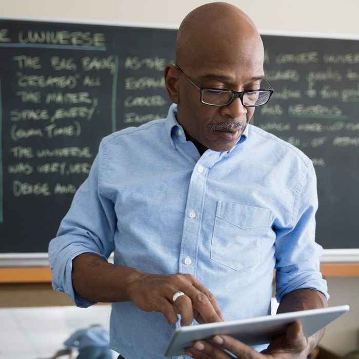 Man holding tablet with chalkboard in background