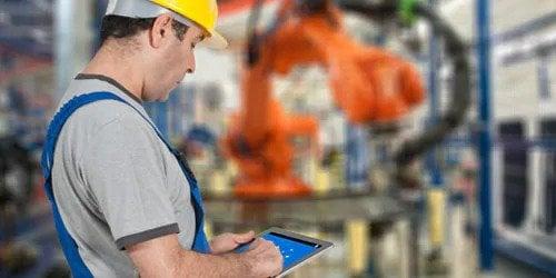 Man wearing helmet using tablet in a factory