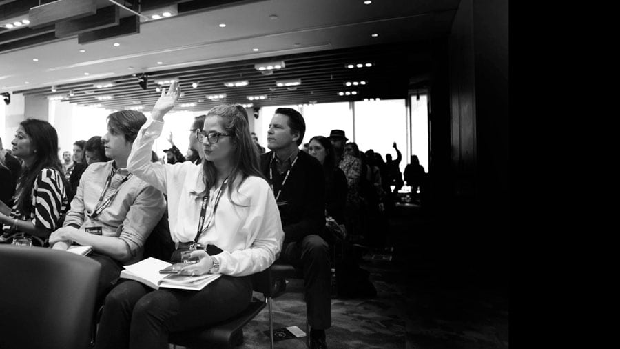 black and white image of people listening to a conference speech