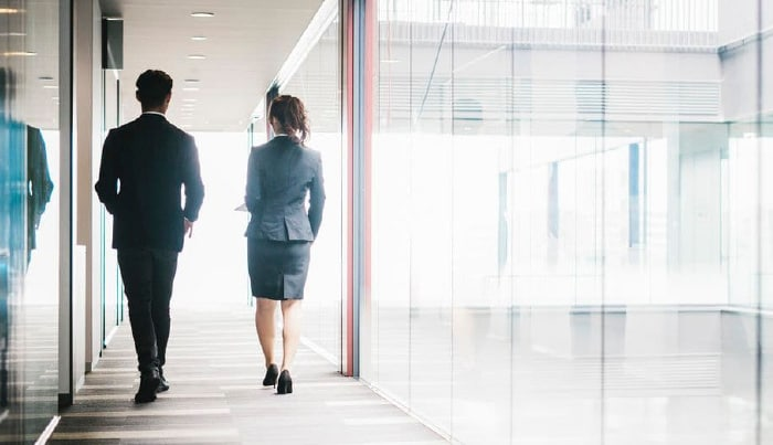 businessman and businesswoman walking in hallway
