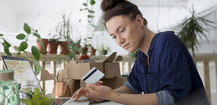 woman at desk with laptop and credit card