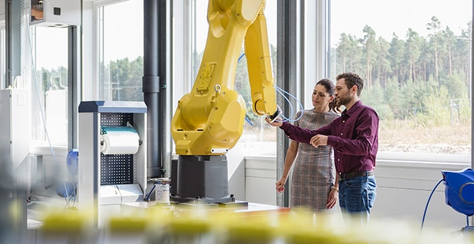 2 people using a robotic arm on a factory