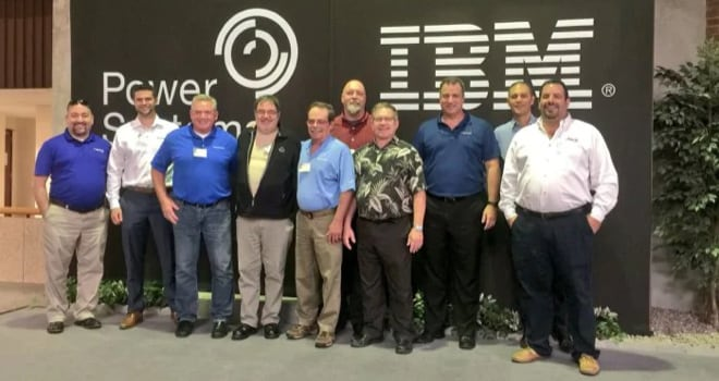 champions standing together in front of a IBM banner