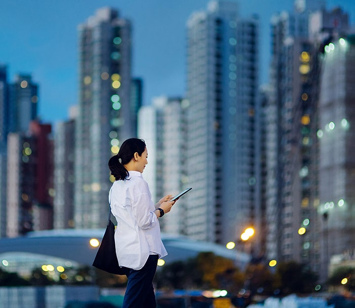 Person using mobile device walking in the city