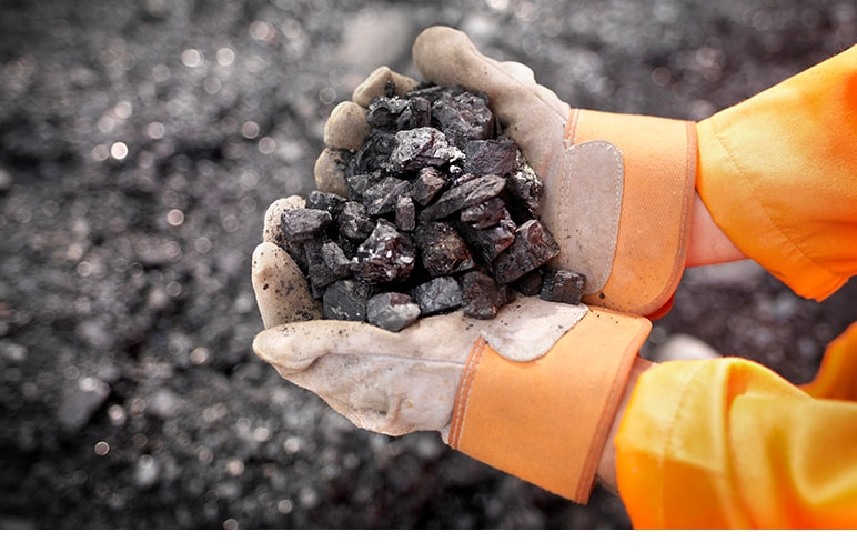 Hands wearing safety gloves and holding minerals