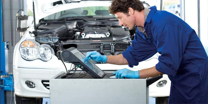 Automotive technician working on a laptop