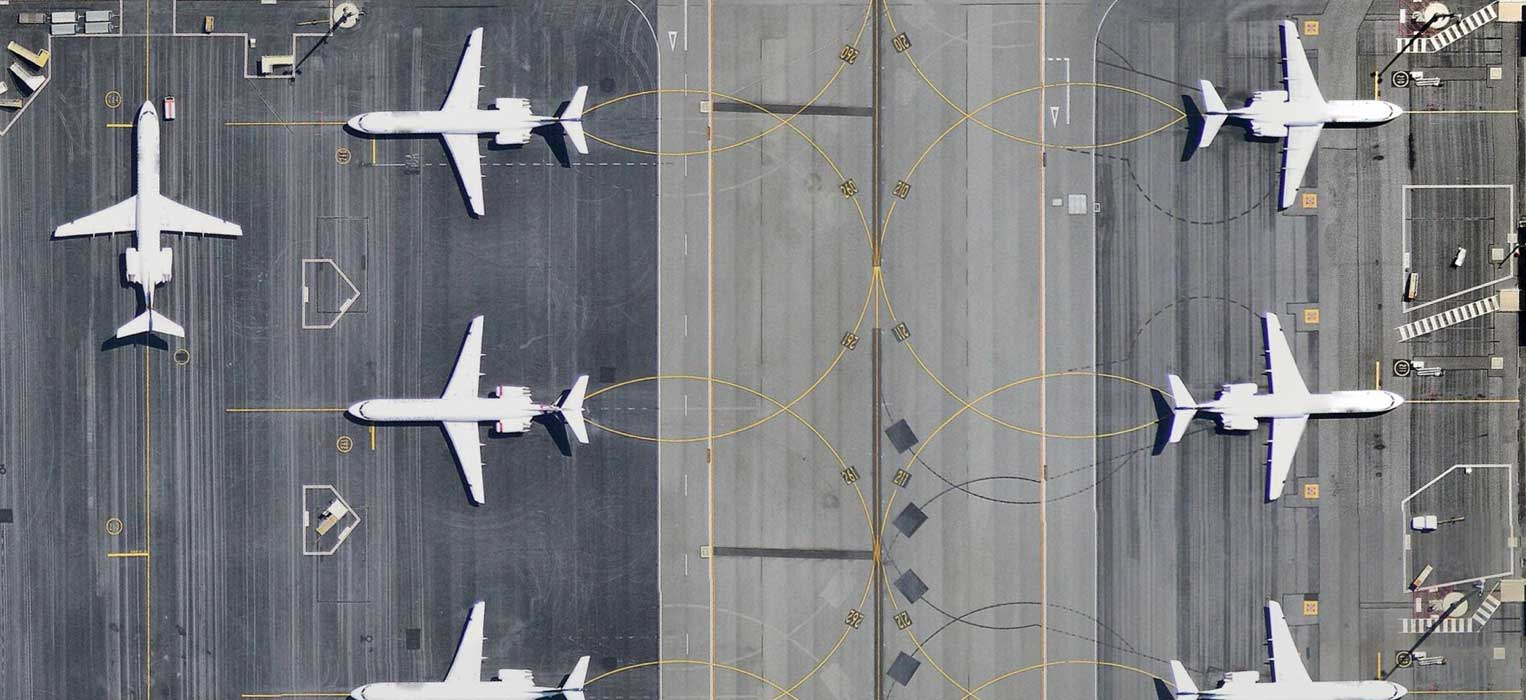 Multiple planes parked along an airport runway