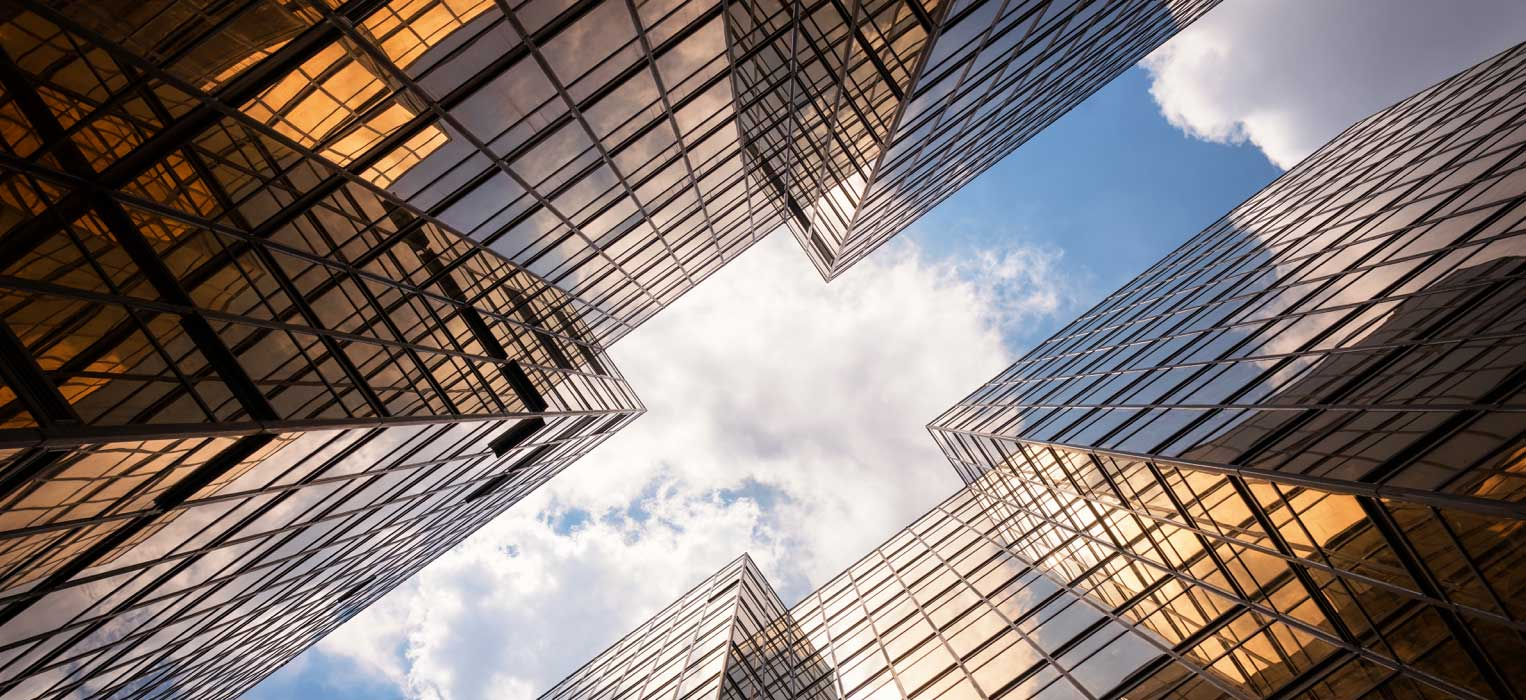 View of the sky looking up through highrise buildings