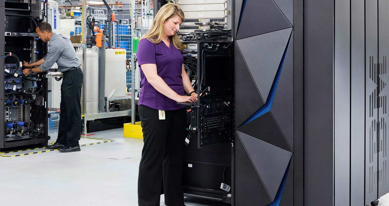 woman in a server room operating a computer