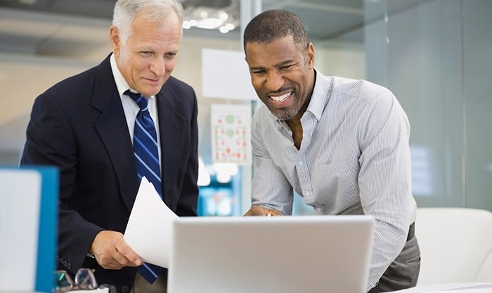 Two men looking happily at a computer screen