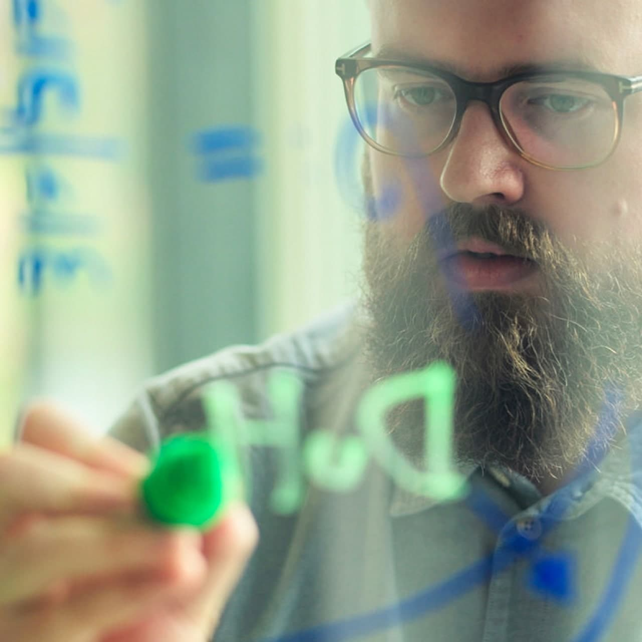 man wign a beard and wearing glasses writting on a glass panel