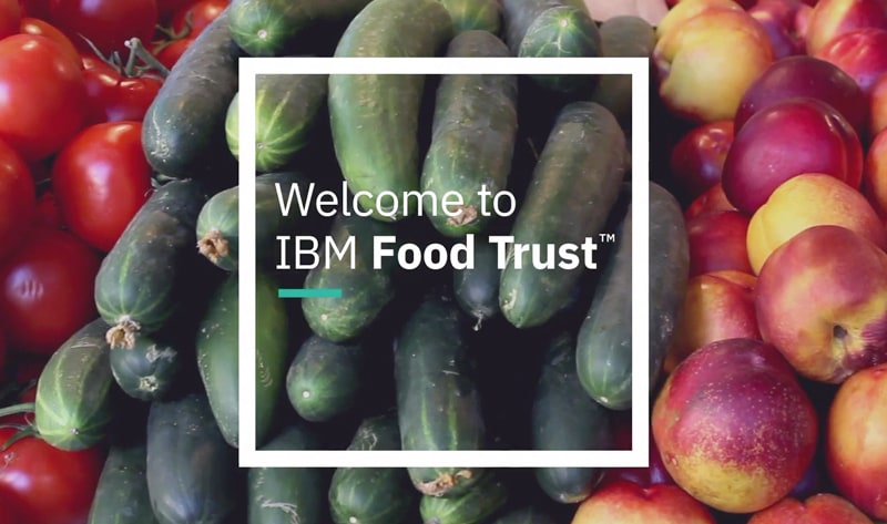 "Vegetables stand with tomatos, cuccumbers and apples, ""Welcome to IBM Food Trust"""