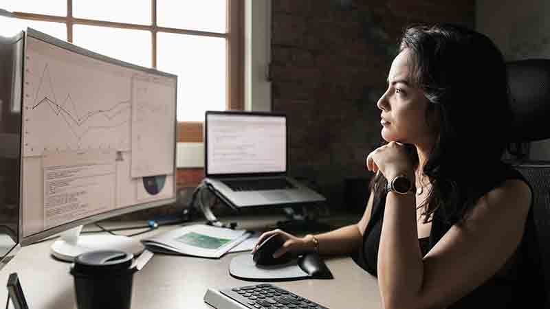 Woman working in front of multiple monitors