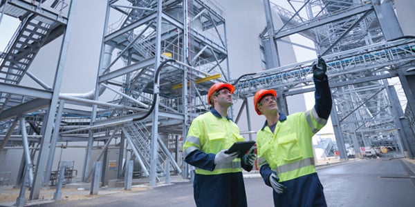 Two engineers pointing around at factory site