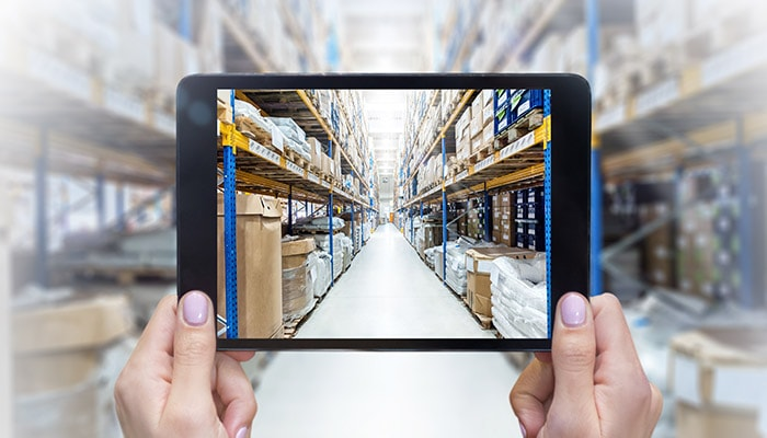 A warehouse filled with inventory is viewed through a tablet screen