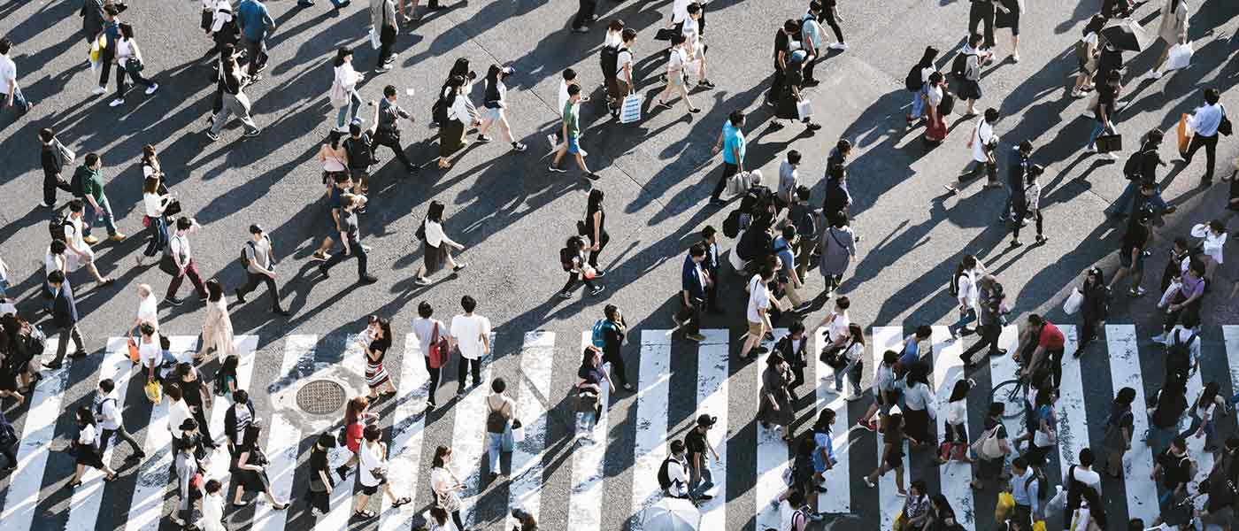 large crowd of people crossing a crosswalk