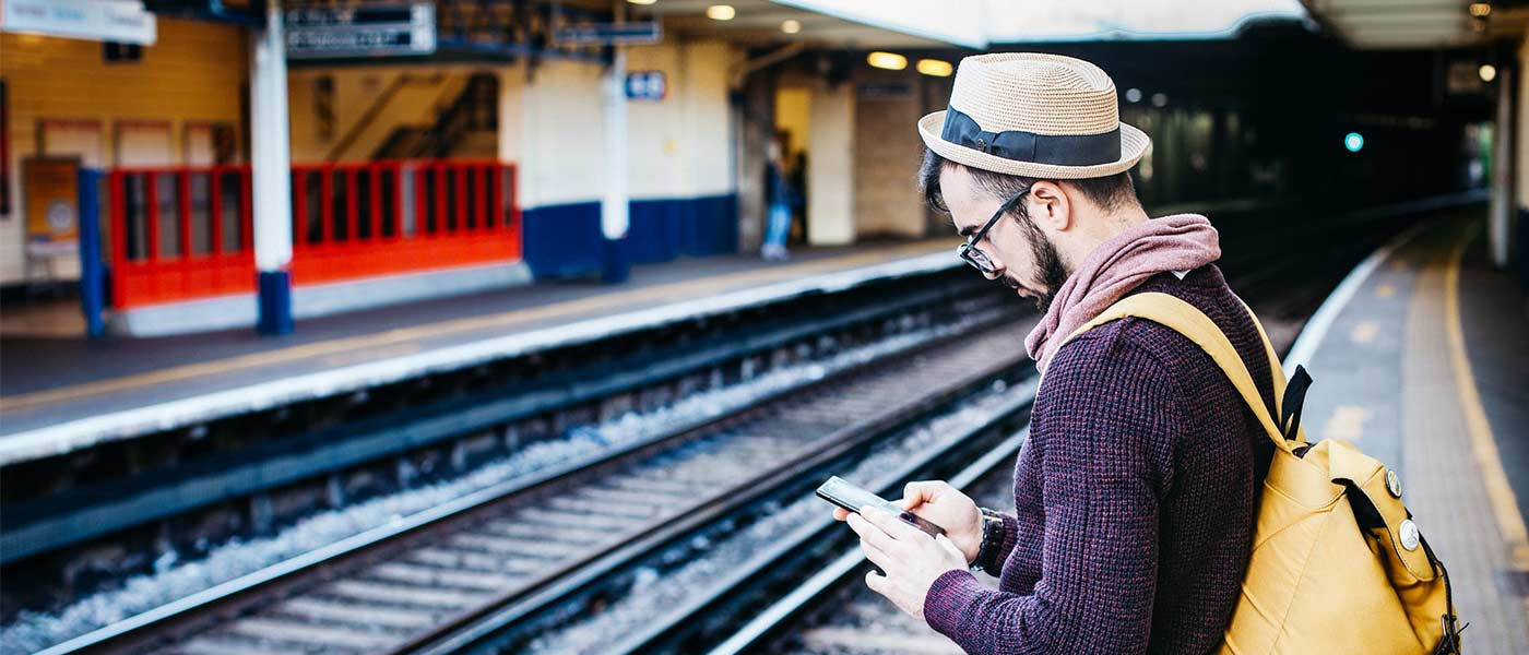 man standing in train station using smartphone