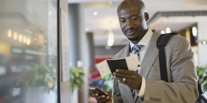 A man with a cellphone looking at his passport