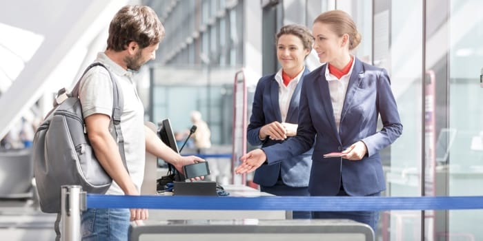 A customer and two airport employees at the boarding platform