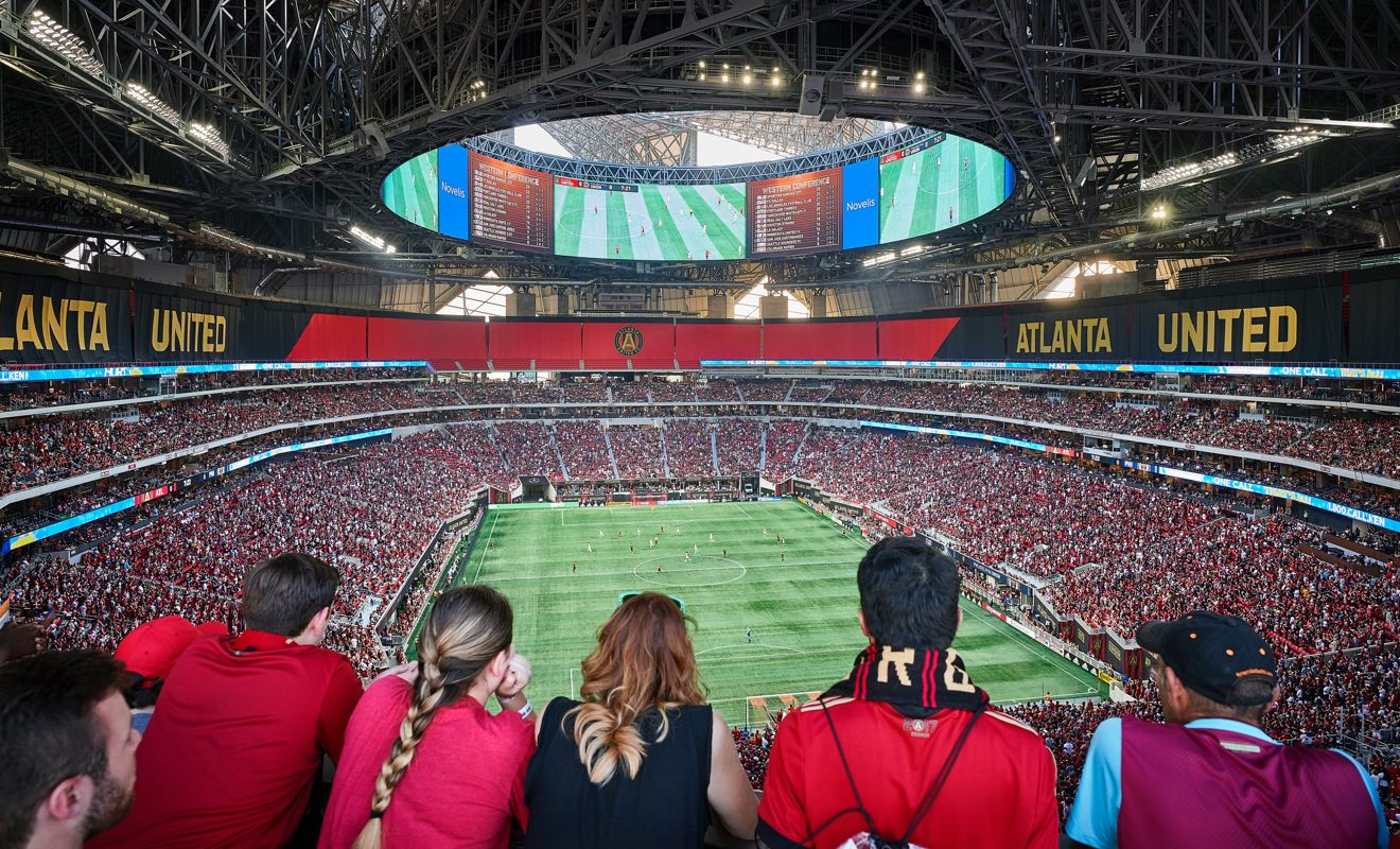 the back side of a row of fans in the fan filled Mercedes Benz Stadium