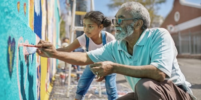 An elder and a children painting a wall