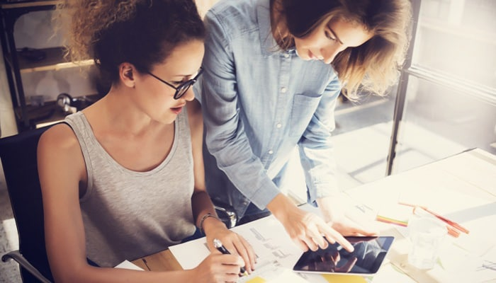 two female figure working with a tablet device