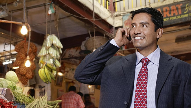 Micro finance banker speaking on phone in a vegetable market