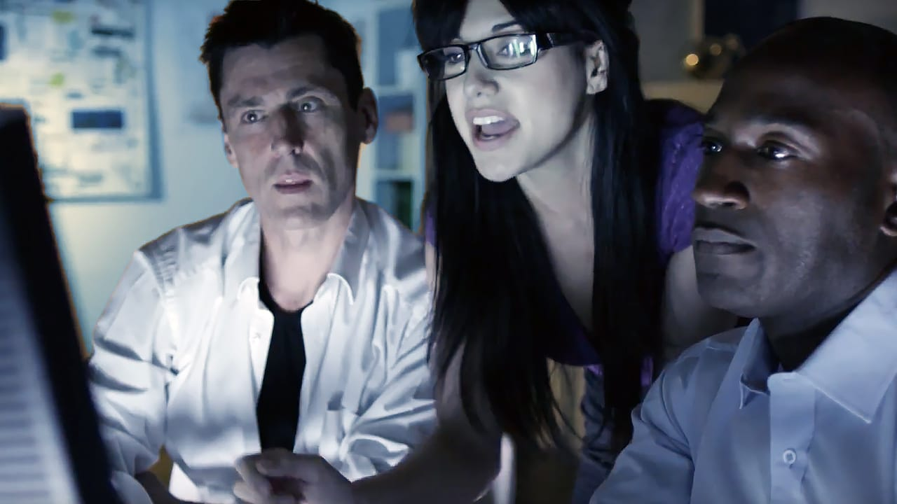 two men and a woman looking at a computer screen