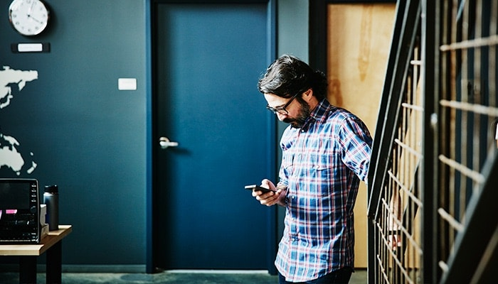 man in an office checking his smartphone