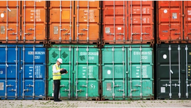 Shipping containers and a worker with a tablet to depict automation