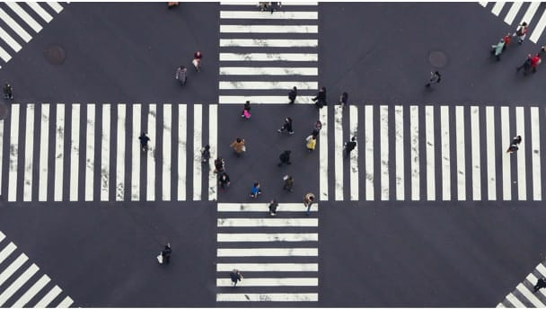 Aerial image of people walking on crosswalks to depict better processes