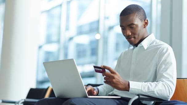 A seated man on laptop looking at a credit card ion his hand