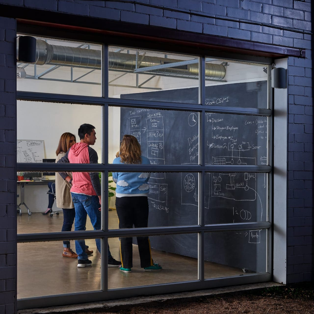 Image of a group of people writing on a chalkboard in a garage-like setting