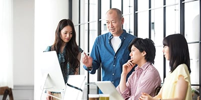 Four people working at a desk looking at a presentation, one is standing and pointing