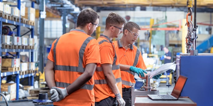 Three factory workers dressed in orange