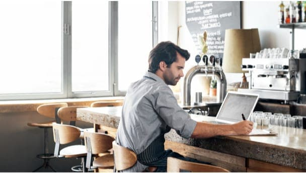 Image of a man on a laptop at a coffeeshop to show how automation transforms invoice processing