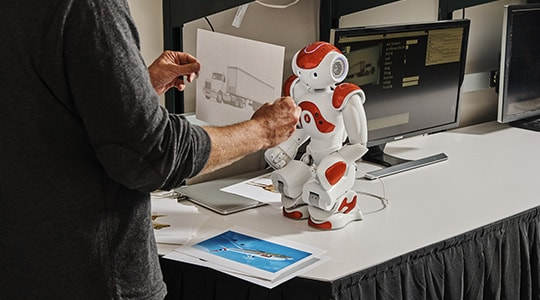 Person training a small robot to recognize pictures