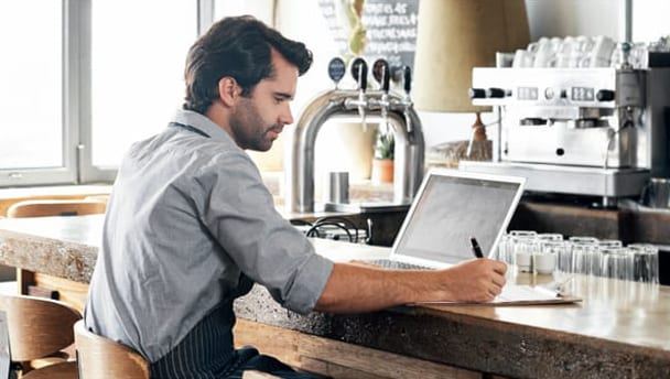 Man on a laptop at a coffeeshop to show how automation transforms invoice processing