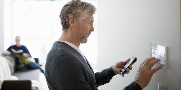 A man configuring his phone and a smart device